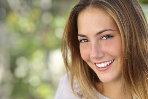 Girls with straight teeth smiling at Nick Romanides Orthodontics